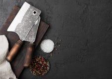 Scure d'annata del coltello della carne sul tagliere d'annata e sul fondo di pietra nero della tavola Utensili del macellaio Sale fotografie stock libere da diritti