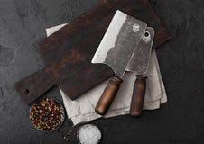 Scure d'annata del coltello della carne sul tagliere d'annata e sul fondo di pietra nero della tavola Utensili del macellaio Sale immagini stock