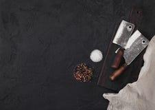 Scure d'annata del coltello della carne sul tagliere d'annata e sul fondo di pietra nero della tavola Utensili del macellaio Sale fotografia stock