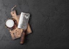 Scure d'annata del coltello della carne sul tagliere d'annata e sul fondo di pietra nero della tavola Utensili del macellaio Spaz immagini stock