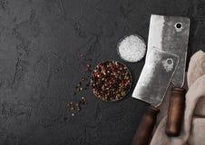 Scuri d'annata del coltello della carne sul fondo di pietra nero della tavola Utensili del macellaio Sale e pepe Spazio per testo fotografia stock
