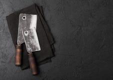 Scuri d'annata del coltello della carne sul fondo di pietra nero della tavola Utensili del macellaio Spazio per il vostro testo fotografia stock libera da diritti