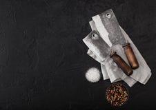 Scuri d'annata del coltello della carne sull'asciugamano di cucina e sul fondo di pietra nero della tavola Utensili del macellaio immagine stock libera da diritti
