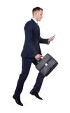 Scurrying businessman with his briefcase and mobile phone on white Royalty Free Stock Photography