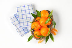 Scuttle of ripe tangerines. And checkered dishtowel on white background Stock Images