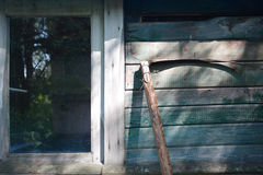 Scythe. Wall of the old rural shed Stock Image