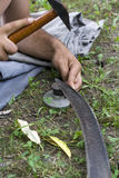 Scythe sharpen. Man lying on grass and whets a scythe with a special hammer Stock Photo