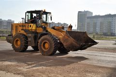 SDLG Earthmover on Road. Modern SDLG LG953 earthmover machine in dirt stained yellow travels along an empty Road Royalty Free Stock Image