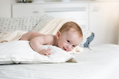Sdorable behandla som ett barn pojkekrypning på stor säng på sovrummet Arkivfoton