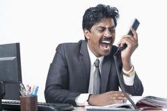 Södra indisk affärsman som arbetar i ett kontor och ropa Arkivbild
