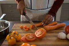 Seção meados de da cenoura do corte da mulher no contador Foto de Stock