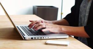 Seção meados de do executivo fêmea que senta-se na mesa e que usa o portátil filme