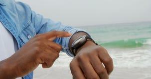 Seção meados de do homem afro-americano que usa o smartwatch na praia 4k filme