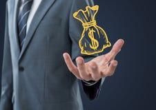 Seção meados de do homem de negócio com garatuja amarela do moneybag à disposição contra o fundo da marinha Foto de Stock Royalty Free