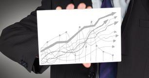 Seção meados de do homem de negócio com o cartão que mostra o gráfico cinzento contra o fundo cinzento Fotografia de Stock