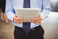 Seção meados de do homem de negócios que usa a tabuleta digital Imagem de Stock Royalty Free