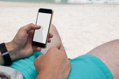Seção meados de do homem que usa o telefone celular na praia foto de stock