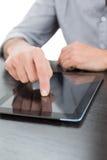 Seção meados de um homem de negócios que usa a tabuleta digital na tabela Foto de Stock Royalty Free