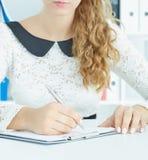 Seção meados de um secretário fêmea que toma notas em uma prancheta Foto de Stock