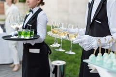 A seção mestra de garçons profissionais no vinho uniforme do serviço e os petiscos durante a restauração do bufete party, evento  imagem de stock
