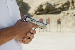 Seção mestra de um homem que guarda a arma da mão Fotografia de Stock Royalty Free