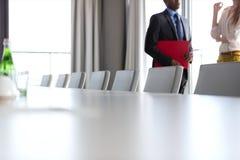 Seção mestra do homem de negócios e da mulher de negócios que estão pela tabela de conferência no escritório Fotografia de Stock