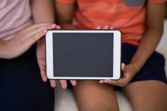 Seção mestra do terapeuta fêmea e do menino que mostram a tabuleta digital ao sentar-se na cama fotos de stock royalty free