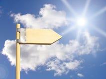 Señal de dirección bajo el sol Foto de archivo