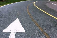 Señal de dirección blanca de la flecha del camino en la carretera de asfalto Foto de archivo libre de regalías
