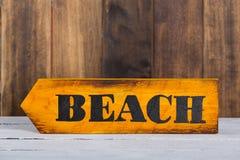 Señal de dirección con la playa Imagenes de archivo