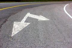 Señal de dirección de la flecha del camino en la carretera de asfalto, transporte Foto de archivo libre de regalías