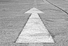 Señal de dirección de la flecha en el camino fotos de archivo