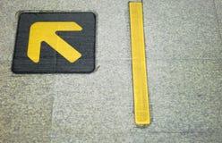 Señal de dirección Muestra amarilla de la flecha en el piso de mármol en el stati del tren Foto de archivo