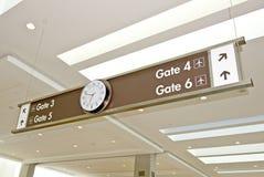 Señal de direcciones del aeropuerto con el reloj Fotos de archivo libres de regalías