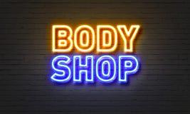 Señal de neón del body shop en fondo de la pared de ladrillo Foto de archivo libre de regalías