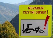 Señal de peligro áspera del camino, con el dibujo de un motorista que cae de su motocicleta imagen de archivo