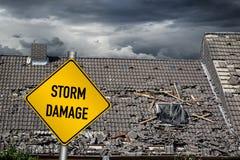 Señal de peligro amarilla del daño delante del tejado dañado tormenta del hou foto de archivo