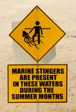 Señal de peligro amarilla en la playa fotografía de archivo