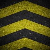 Señal de peligro amarilla y negra en textura del asfalto Imágenes de archivo libres de regalías