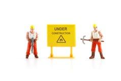 Señal de peligro bajo construcción con la figura miniatura labo Imagenes de archivo