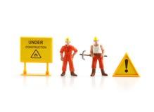 Señal de peligro bajo construcción con la figura miniatura labo Imágenes de archivo libres de regalías