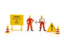 Señal de peligro bajo construcción con la figura miniatura labo Fotografía de archivo