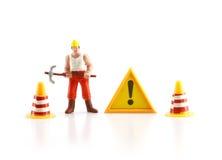 Señal de peligro bajo construcción con la figura miniatura labo Foto de archivo