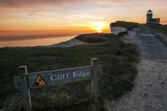 Señal de peligro con el faro el al frente con playas en la puesta del sol Foto de archivo