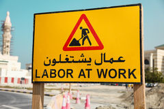 Señal de peligro del camino - trabaje en el trabajo escrito en un árabe y una lengua inglesa Fotos de archivo