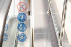 Señal de peligro en la escalera móvil en la estación de metro Opinión superior del foco selectivo de escaleras móviles con las mu Foto de archivo libre de regalías
