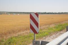 Señal de peligro en un fondo borroso de un campo de trigo foto de archivo