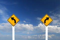 Señal de peligro izquierda y derecha de la vuelta con el cielo azul Fotos de archivo