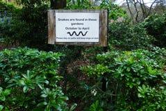 Señal de peligro de la serpiente en un parque foto de archivo