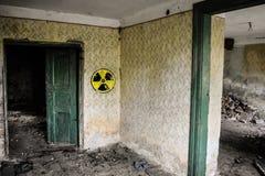 Señal de peligro radiactiva en la pared sucia del grunge en el edificio abandonado de la zona de exclusión Atmósfera de Chernóbil imagenes de archivo